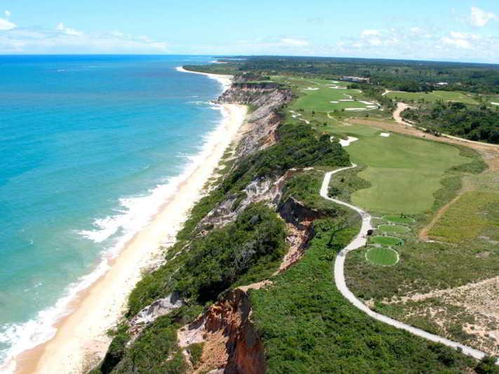 Vista aérea com detalhes na faixa de pura natureza frente mar com campo de golf
