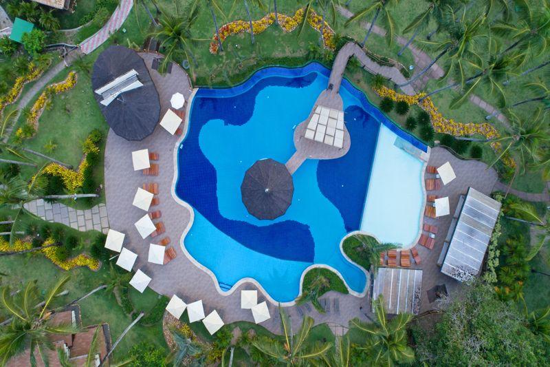 Aérea da piscina do resort com suas cores variadas em meio a natureza