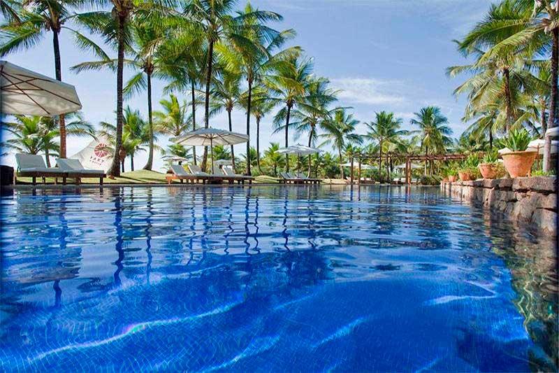 Agua azul da piscina se mistura a natureza exuberante