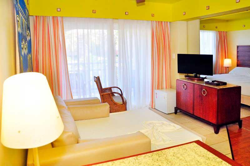 Apartamentos Sauípe com detalhes da cama casal e televisão