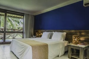 Cama casal com detalhes azul na acomodação Bangalô Luxo