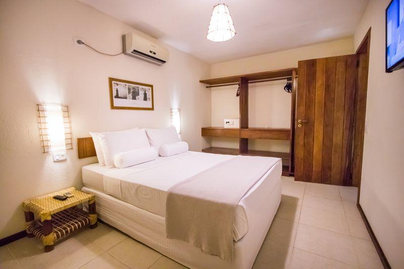 Lateral cama casal branca com televisão