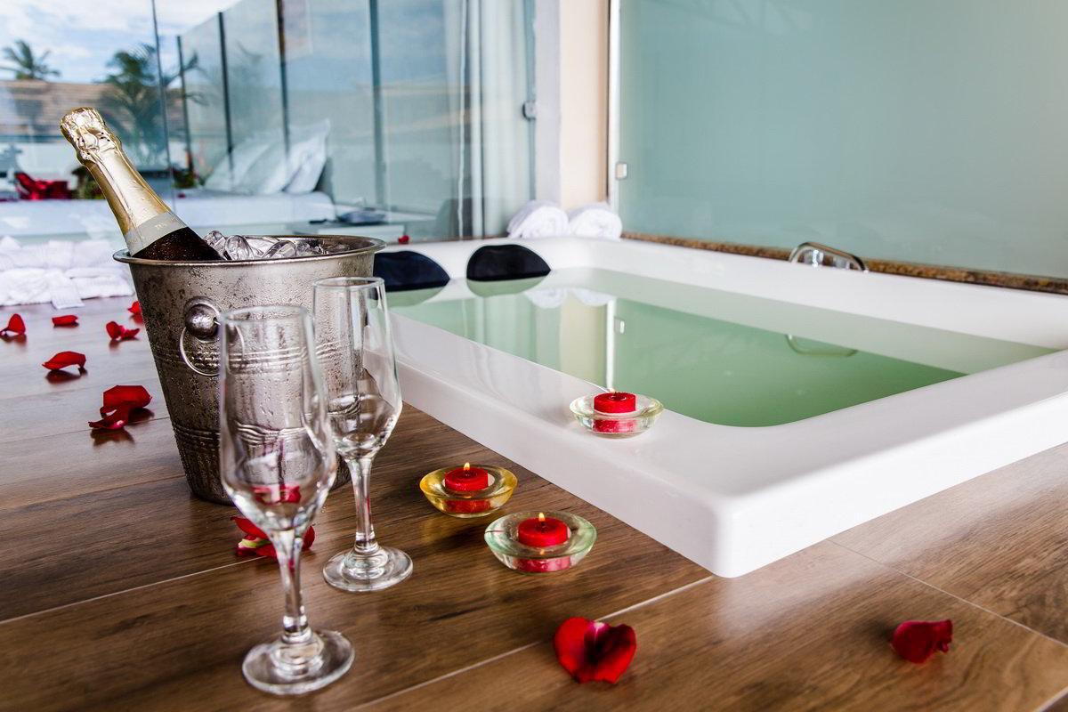 Espumantes junto a banheira e detalhes do amenities