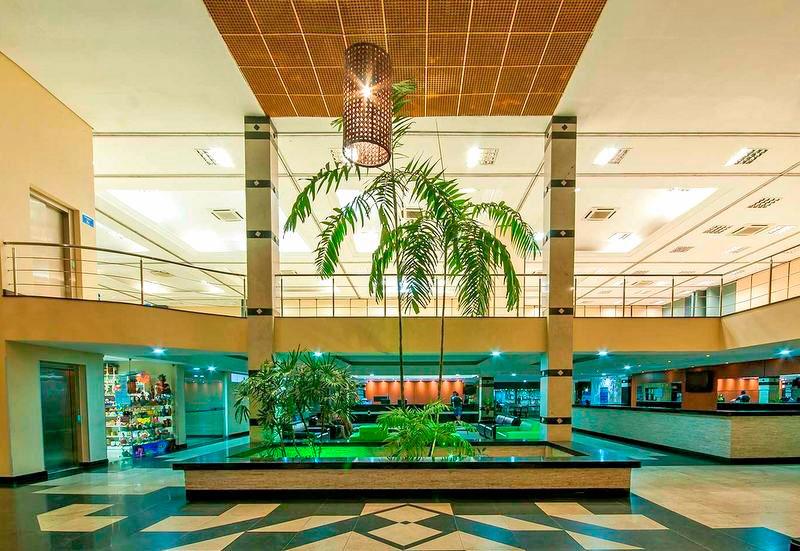 Vista panoramica do lobby contando com serviços de recepção e lojas de produtos