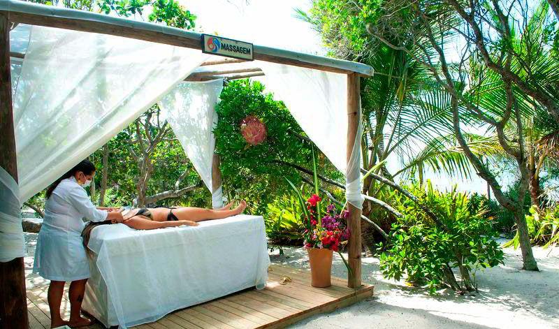 Massagem sendo aplicado em meio a natureza com espaço preparado com cama para aplicação