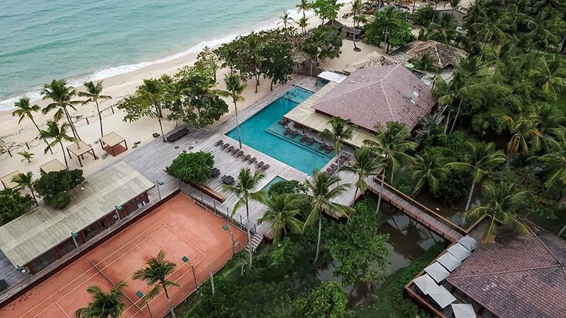 Vista aérea da piscina com hotel frente mar